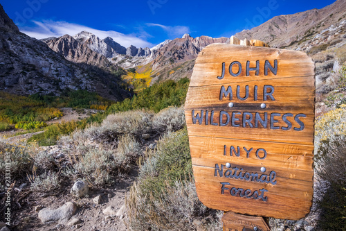 Sign posted at the entrance to the John Muir Wilderness, in the Inyo National Forest; Eastern Sierra mountains, California; McGee valley visible in the background; beautiful sunny fall day