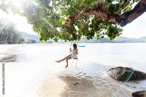 Poster Lieu connus d Asie Beautiful young woman traveler swinging on a swing on a tropical island in the background of amazing landscape