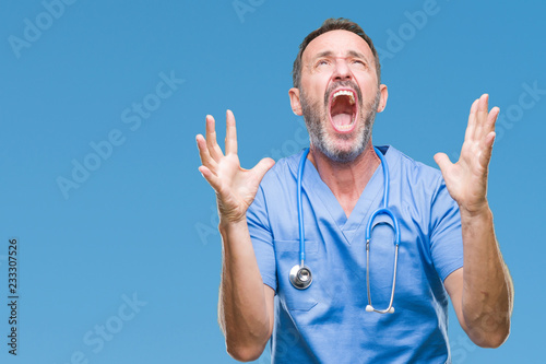 Middle age hoary senior doctor man wearing medical uniform over isolated background crazy and mad shouting and yelling with aggressive expression and arms raised Fototapeta