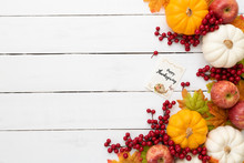 Top View Of  Autumn Maple Leaves With Pumpkin And Red Berries On White Wooden Background. Thanksgiving Day Concept.