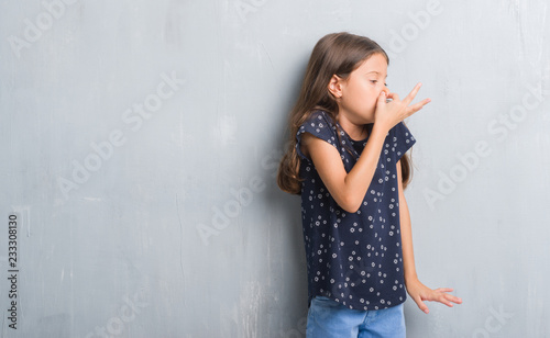 Fotografie, Tablou  Young hispanic kid over grunge grey wall smelling something stinky and disgusting, intolerable smell, holding breath with fingers on nose