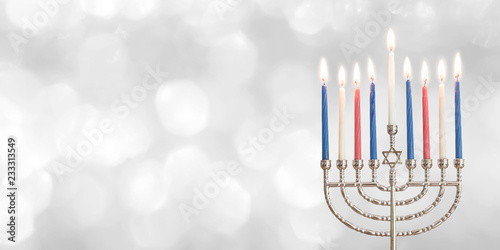 Hanukkah Chanukah Jewish holiday background with menorah (Judaism candelabra) for Festival of Lights and Feast of Dedication with burning candles and traditional on white silver winter snow bokeh