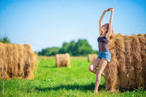 Photo  Young girl enjoys nature raising her hands up near a haystack