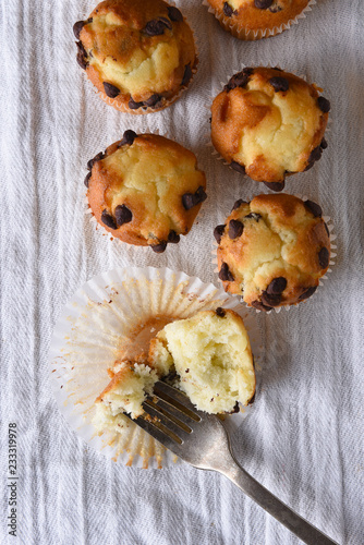 Photo  Overhead view of a group of mini chocolate chip muffins on a kitchen towel