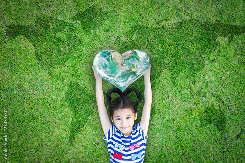 Photo World kindness day concept with happy kid raising heart planet on ecological friendly natural green lawn