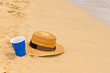 Plastic cup and hat on the beach sands as vacation concept.