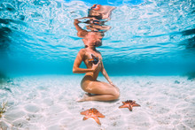 Beautiful Woman Swimming With Starfish, Underwater Photo In Tropical Ocean, Bahamas Island