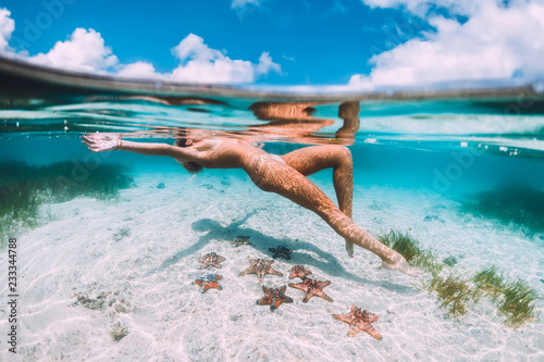 Beautiful woman floating and relax in tropical ocean with starfish, underwater photo