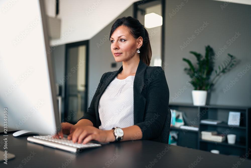 Fototapeta Portrait of beautiful businesswoman working on computer in modern office.