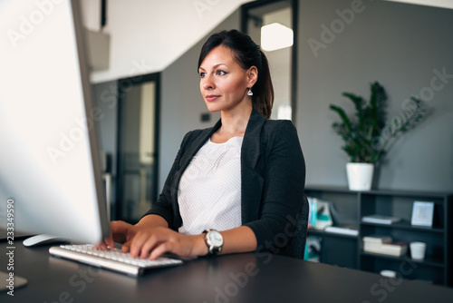 Portrait of beautiful businesswoman working on computer in modern office.
