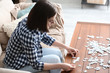 Young woman doing jigsaw puzzle at home