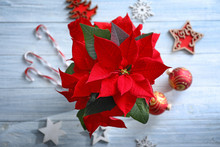 Christmas Flower Poinsettia With Decorations On Wooden Table