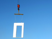 Construction Crane Lifting A Fragment Of The Building Wall. Crane Hook With Concrete Block Isolated On Blue Sky Background