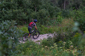 Fototapeta Cyclist in Red Riding the Bike on the Autumn Rocky Trail at Sunset. Extreme Sport and Enduro Biking Concept