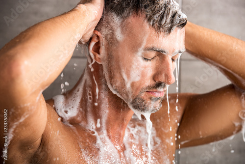 Papel de parede selective focus of adult man with closed eyes washing foam in shower