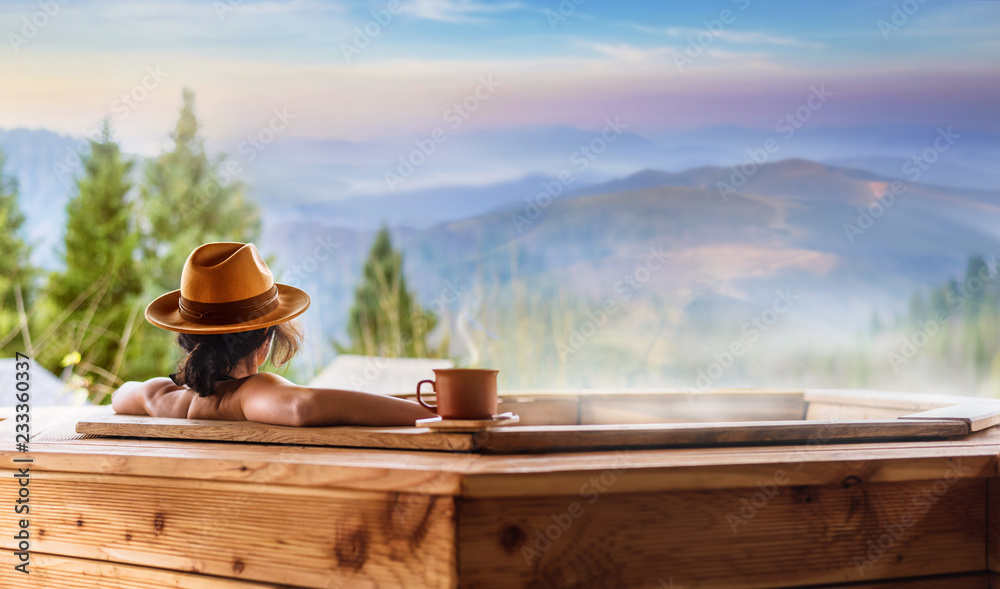 Fototapeta Young woman in an open air bath with view of the mountains.