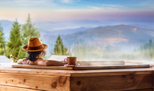 Young Woman In An Open Air Bath With View Of The Mountains.