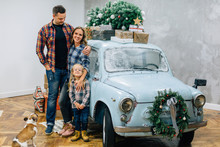 Beautiful Family In Checked Shirts Standing With Dog Near Blue Retro Car With Presents On The Roof. Family In Stylish Decorated Interior Studio For Christmas And New Year Holidays