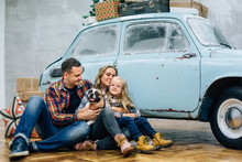 Beautiful Family In Checked Shirts Sittng With Dog Near Blue Retro Car With Presents On The Roof. Mother Father Daughter In Stylish Decorated Interior Studio For Christmas And New Year Holidays