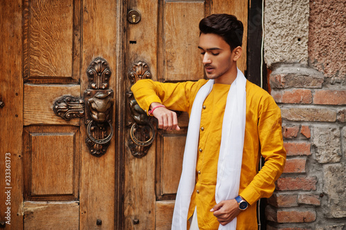 Fotografie, Obraz  Indian stylish man in yellow traditional clothes with white scarf posed outdoor against old gates