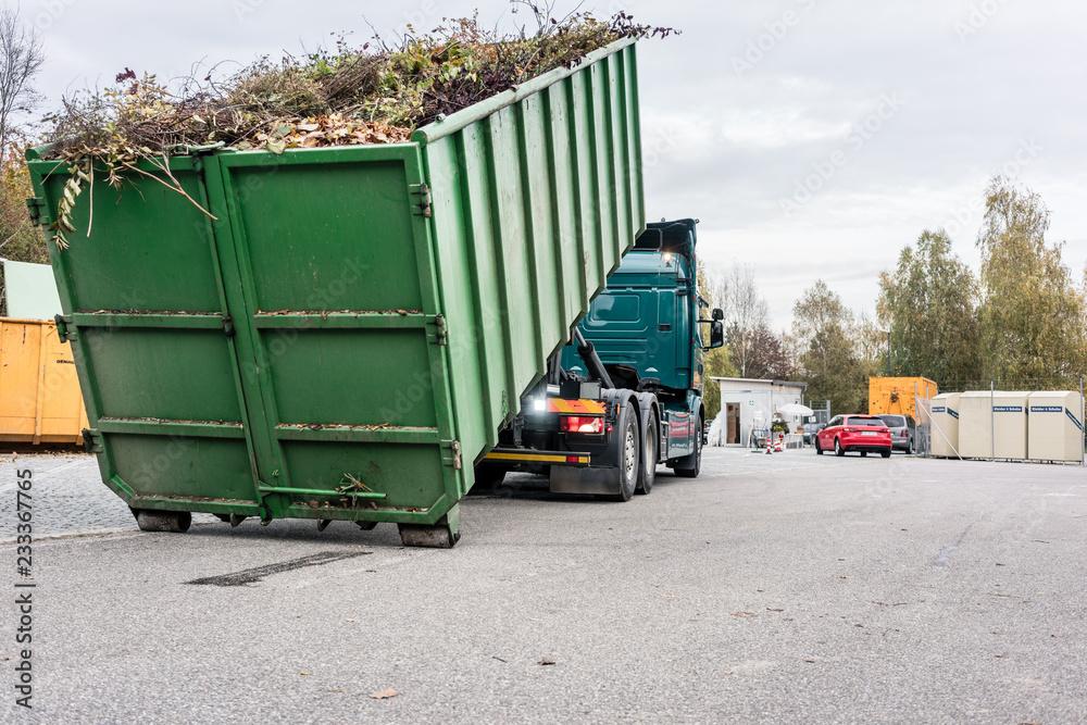 Fototapeta LKW lädt Container mit Grünschnitt auf dem Wertstoffhof auf