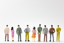 A Group Of Miniature Business People Stand On White Background Back View.