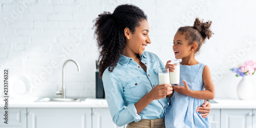 Photo smiling african american mother and daughter holding glasses of milk in kitchen