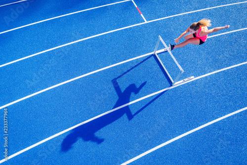 Top view of female runner crossing hurdle on tartan track