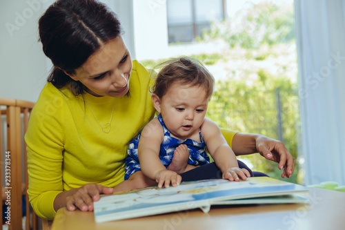 Mother and baby daughter looking at children's book
