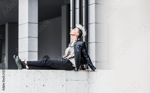 Foto op Plexiglas Baksteen muur Punk woman sitting on a wall with closed eyes