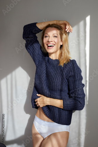 Portrait of laughing blond woman wearing knit pullover and panties leaning against wall