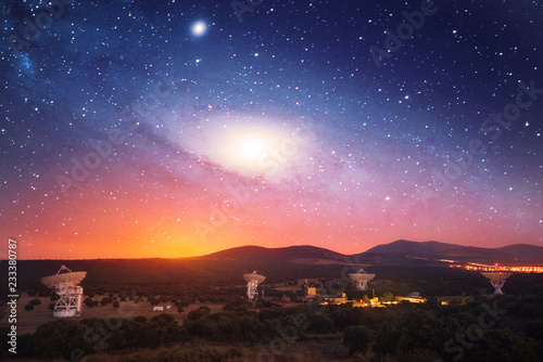 Radio telescopes at night with galaxy in the sky