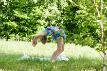 A Little Girl Doing A Yoga Backbend Wheel Pose On A Green Grass. Stretching And Fitness Training On The Summer Meadow, Healthy Childhood