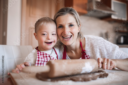 Fototapeta  A portrait of handicapped down syndrome boy with his mother indoors baking