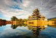 Leinwanddruck Bild - Matsumoto Castle in Matsumoto City Nagano Prefecture In autumn, the change of time from day to night The golden light of the sun shines to the castle with a reflection of the water