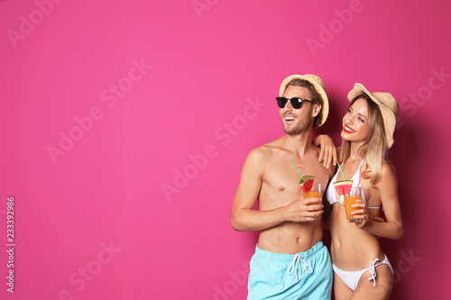 Happy young couple in beachwear with cocktails on color background. Space for text