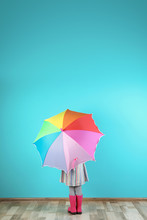 Little Girl With Rainbow Umbrella Near Color Wall. Space For Text