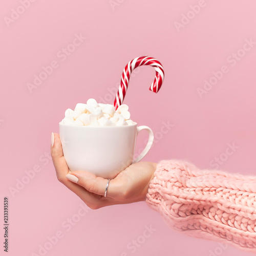 Female hands in knitted sweater holding cup of marshmallows and Christmas candy cane on pink background Flat Lay copy space. Winter traditional food Festive decor celebration presents Xmas holiday