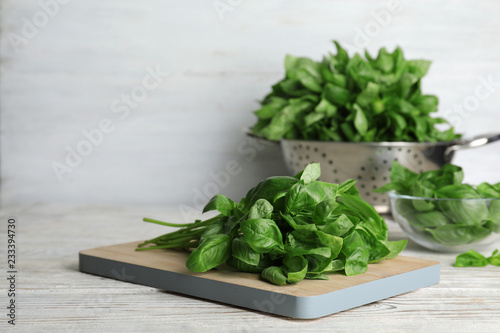 Foto op Canvas Aromatische Wooden board with basil leaves on table. Space for text