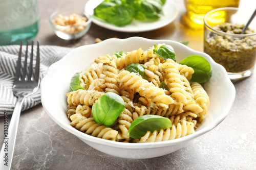 Plate of delicious basil pesto pasta served for dinner on table