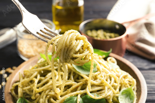 Fork with delicious basil pesto pasta over plate, closeup