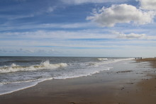 Landscape Of Huge Deserted Sandy Wild Beach With Calm Sea Water At High Tide And Rolling Cloudy Skies Of Deep Blue And Light Shining At Sun Down In Norfolk East  Anglia England On Cold Autumn Day