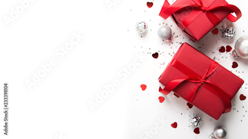 Fototapeta Merry Christmas and Happy Holidays greeting card. New Year. Red gift, present on white background top view. Winter holidays. obraz na płótnie
