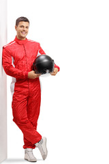 Fototapeta Racer holding a helmet and leaning against a wall