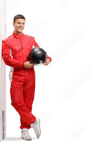 Racer holding a helmet and leaning against a wall
