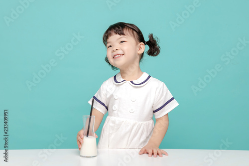Little pretty Asian girl laughing portrait with milk and bread, healthy and happy lifestyle Fototapet