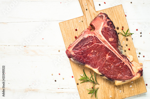 T-bone beef steak on white with spices.