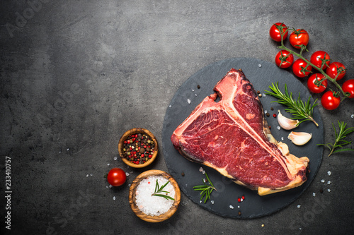 T-bone beef steak on black with spices.