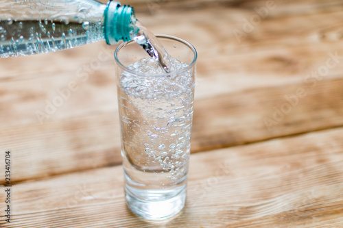 Sparkling water is poured into a glass on a wooden background.
