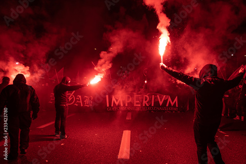 People carry Polish flags and burn flares as they walk across the Poniatowski Bridge during a march marking the 100th anniversary of Polish independence in Warsaw, Poland November 11, 2018.